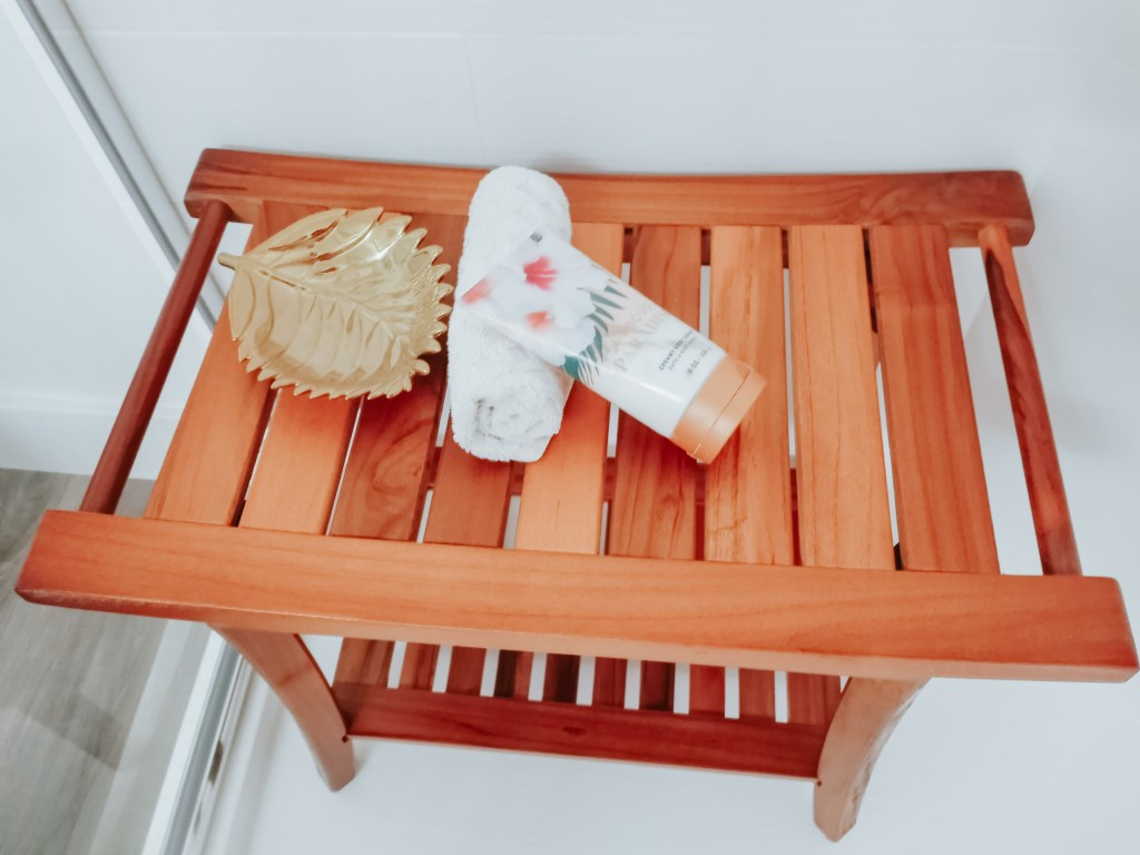 Shower bench with gold leaf tray, towel and body wash