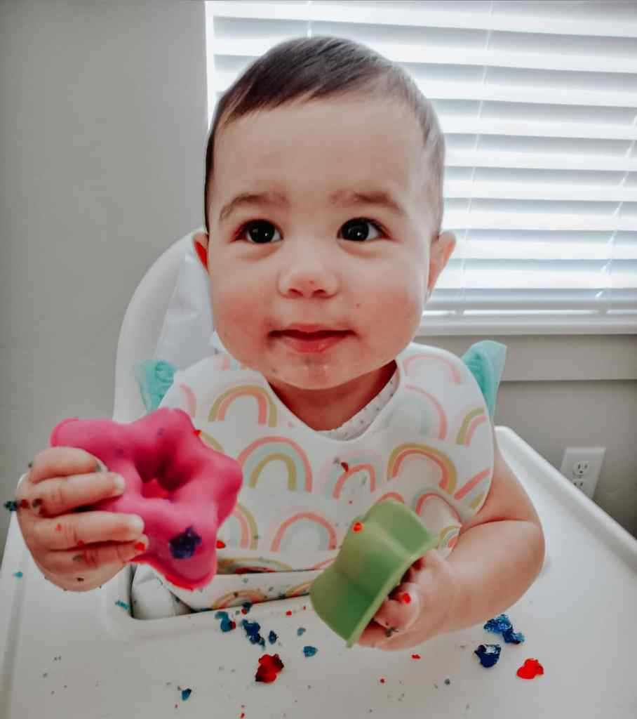 Cute messy baby smiling with jiggler cups