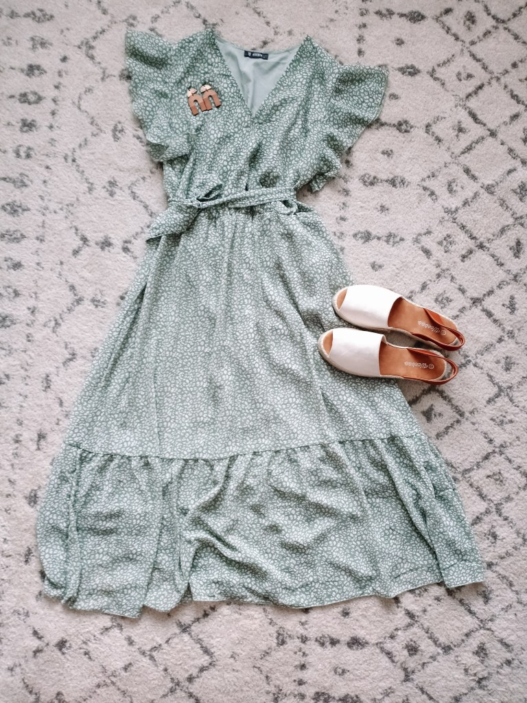 Sage green dress flat lay with cream suede shoes and wooden arch earrings
